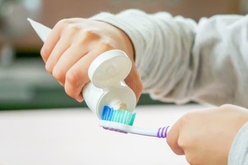 El niño aplica el cepillo de dientes y la crema dental en fondo borroso fotografía de archivo libre de regalías
