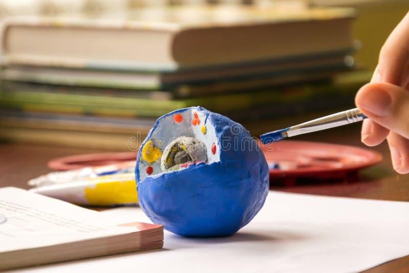 El niño aprende biología, estudia la estructura de la célula La célula se hace de la arcilla y se pinta con témpera foto de archivo libre de regalías