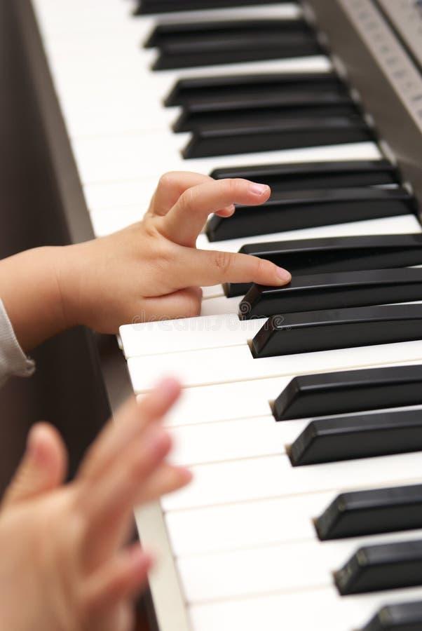 El niño aprende el piano fotografía de archivo