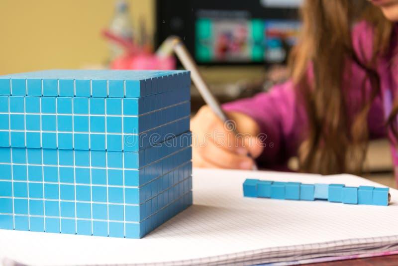 El niño aprende matemáticas, el volumen y la capacidad Para aprender el modelo utiliza un cubo tridimensional foto de archivo libre de regalías
