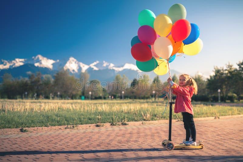 El niño aprende montar la vespa del retroceso en el parque el verano fotos de archivo
