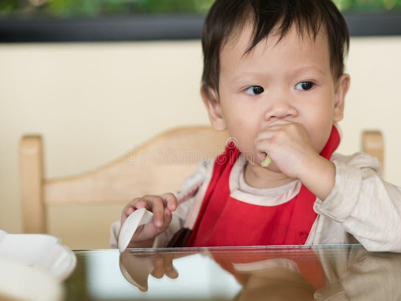 El niño asiático aprende comer la comida mismo imagen de archivo libre de regalías