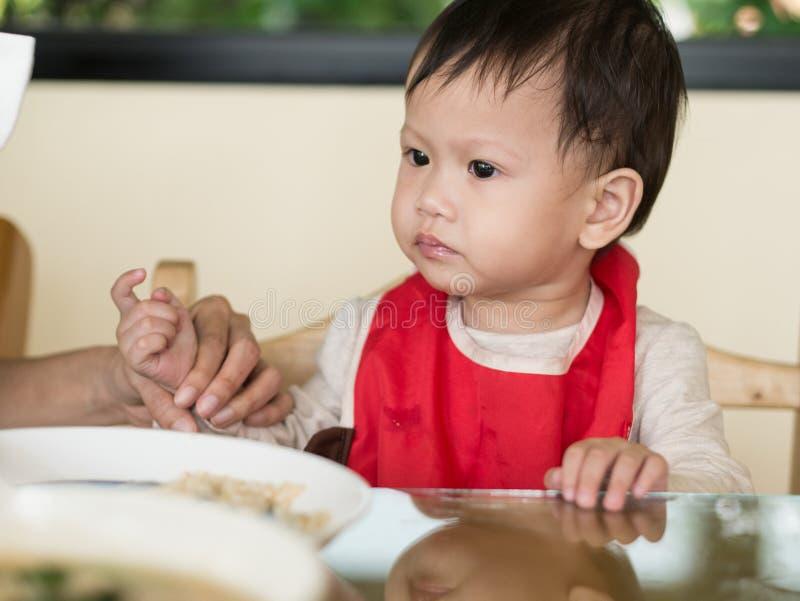 El niño asiático aprende comer la comida mismo imagenes de archivo