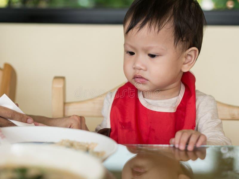 El niño asiático aprende comer la comida mismo imagen de archivo