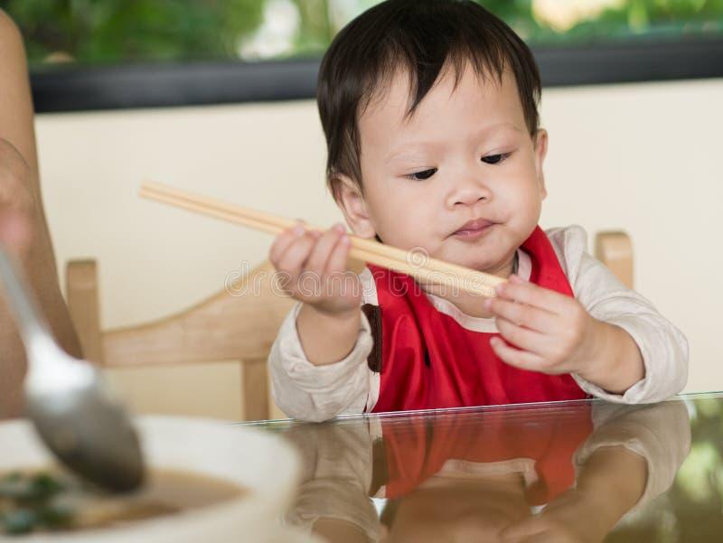 El niño asiático aprende comer la comida mismo que sostiene los palillos imagenes de archivo