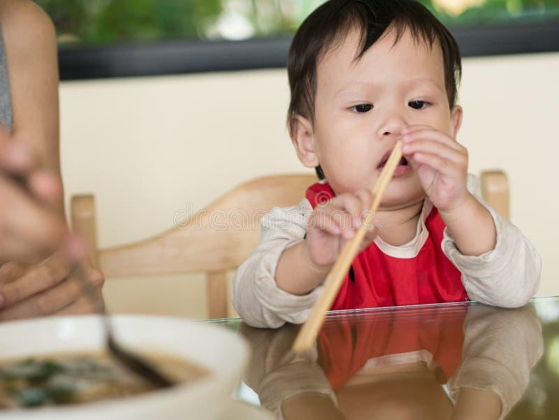 El niño asiático aprende comer la comida mismo que sostiene los palillos fotografía de archivo
