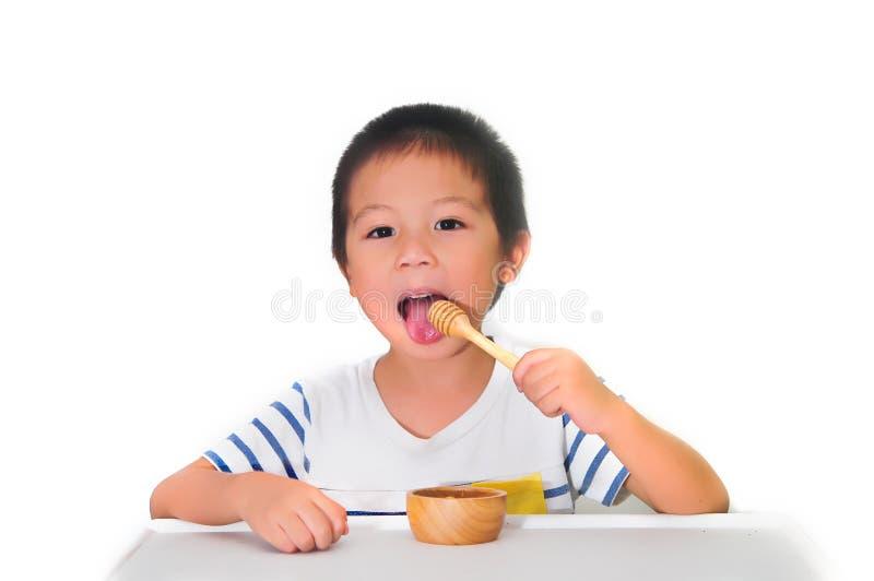 El niño asiático come la miel foto de archivo libre de regalías