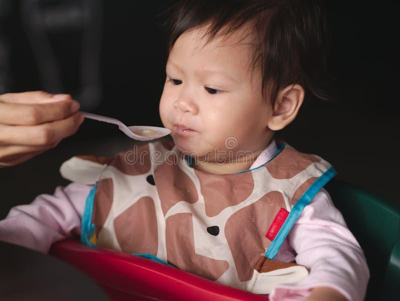 El niño asiático con el babero sucio come la comida por la alimentación de la mamá fotos de archivo