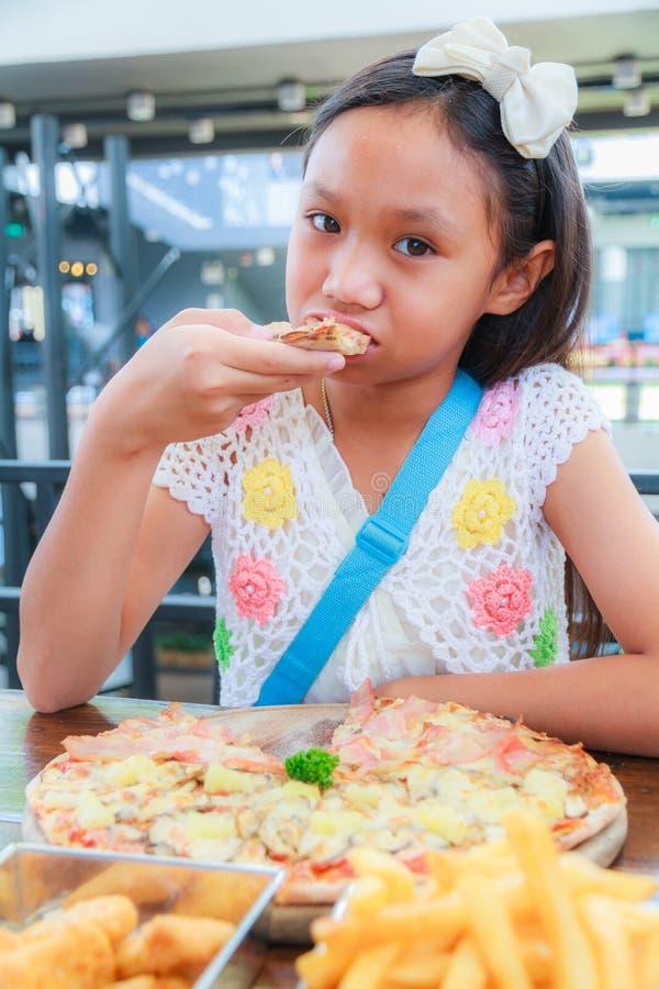 El niño asiático de la muchacha come la pizza fotografía de archivo libre de regalías