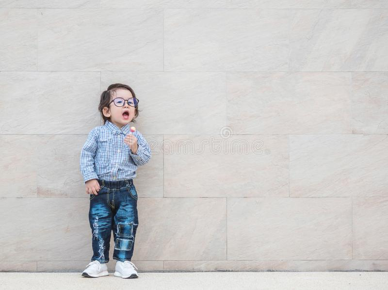 El niño asiático del primer con las lentes en el movimiento feliz con el caramelo en su mano en la pared de piedra de mármol text foto de archivo libre de regalías