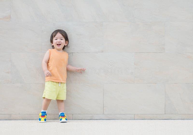 El niño asiático feliz del primer con la cara de la sonrisa en la pared de piedra de mármol texturizó el fondo con el espacio de  fotos de archivo