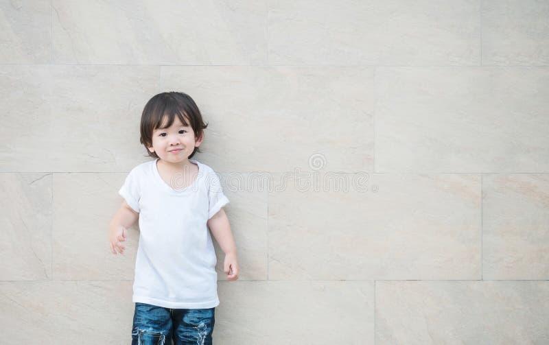 El niño asiático feliz del primer con la cara de la sonrisa en la pared de piedra de mármol texturizó el fondo con el espacio de  imágenes de archivo libres de regalías