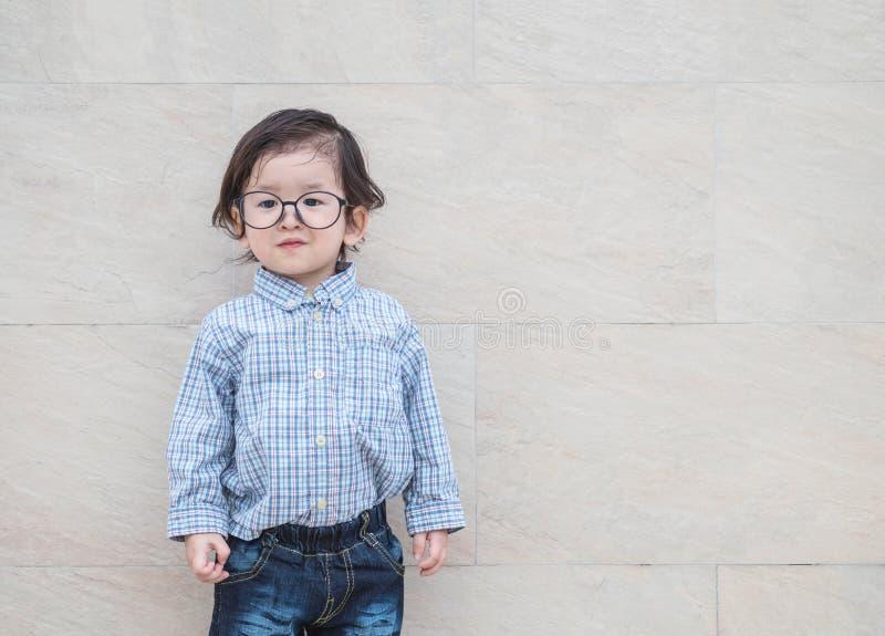 El niño asiático feliz del primer con las lentes en concepto apacible del niño en la pared de piedra de mármol texturizó el fondo imagenes de archivo