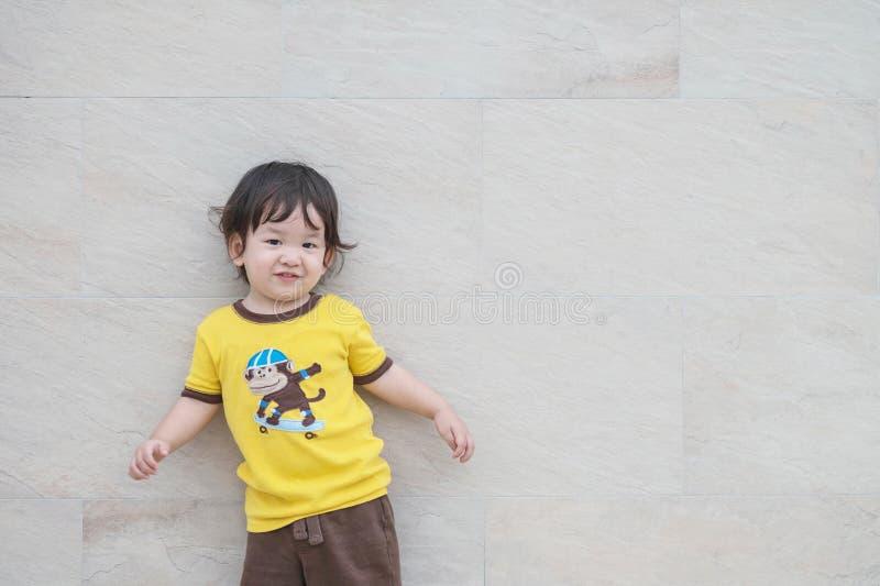 El niño asiático feliz del primer en el movimiento de la danza con la cara de la sonrisa en la pared de piedra de mármol texturiz fotos de archivo
