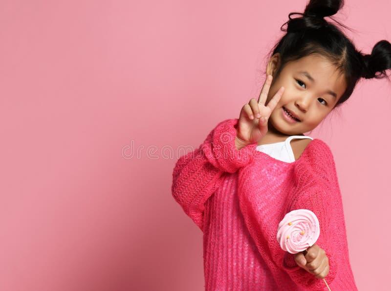 El niño asiático joven feliz de la niña se lame come el caramelo dulce grande feliz del lollypop en rosa imágenes de archivo libres de regalías