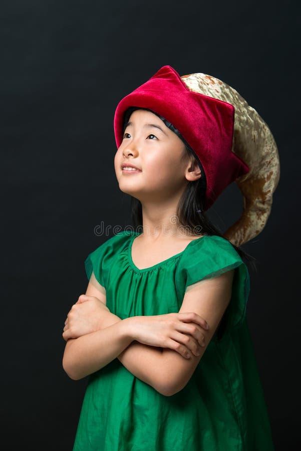 El niño asiático lindo de la muchacha se vistió en sombrero y vestido de hadas del verde en un fondo negro foto de archivo libre de regalías