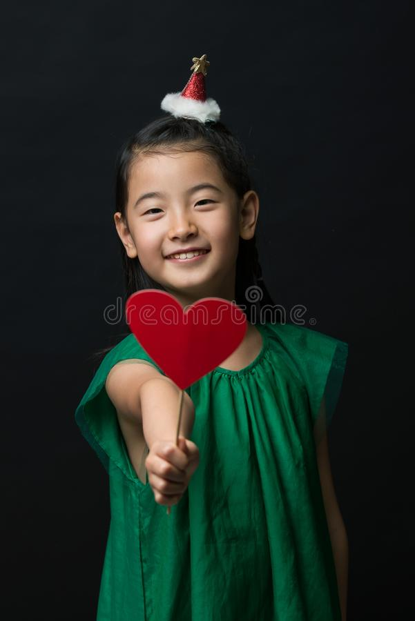 El niño asiático lindo de la muchacha se vistió en un vestido verde que sostenía un ornamento de la Navidad y un palillo del cora fotografía de archivo