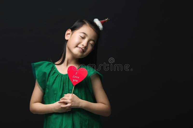 El niño asiático lindo de la muchacha se vistió en un vestido verde que sostenía un ornamento de la Navidad y un palillo del cora foto de archivo libre de regalías