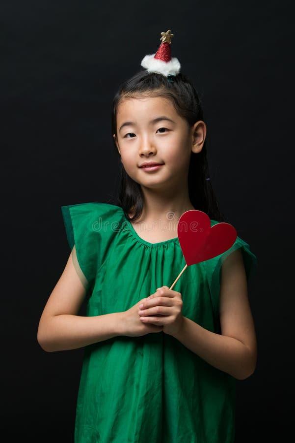 El niño asiático lindo de la muchacha se vistió en un vestido verde que sostenía un ornamento de la Navidad y un palillo del cora imagenes de archivo
