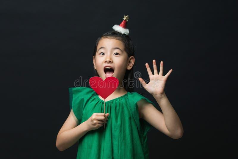 El niño asiático lindo de la muchacha se vistió en un vestido verde que sostenía un ornamento de la Navidad y un palillo del cora fotografía de archivo libre de regalías