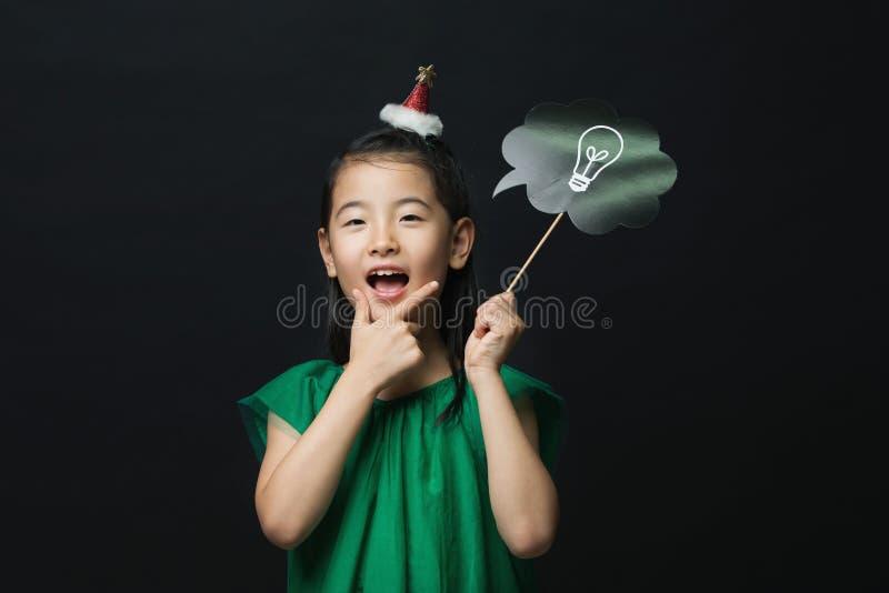 El niño asiático lindo de la muchacha se vistió en un vestido verde que sostenía un palillo del bulbo de la idea con una decoraci imagen de archivo libre de regalías