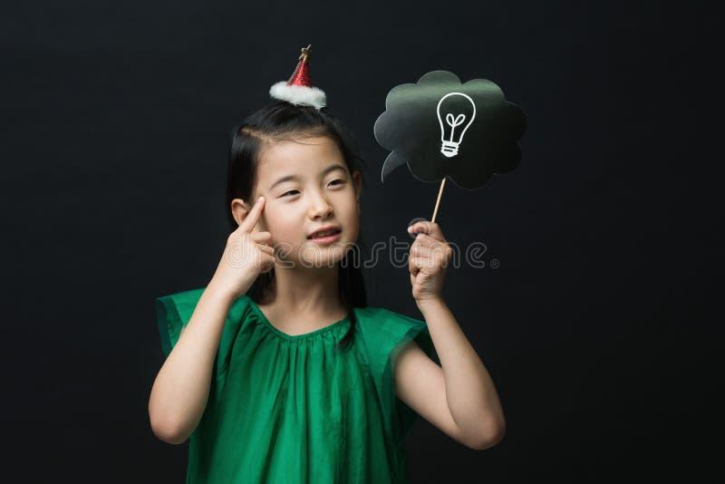 El niño asiático lindo de la muchacha se vistió en un vestido verde que sostenía un palillo del bulbo de la idea con una decoraci fotografía de archivo