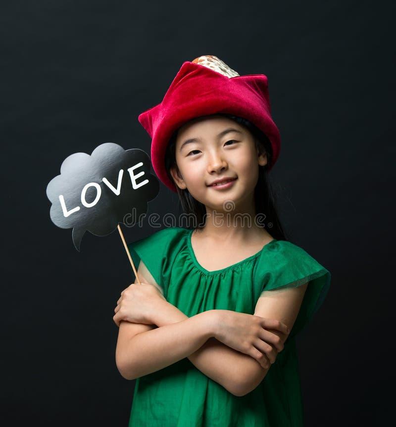 El niño asiático lindo de la muchacha se vistió en un vestido verde que sostenía un sombrero de la Navidad y un palillo del amor  imágenes de archivo libres de regalías