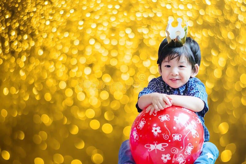 El niño asiático lindo del primer con la corona y el globo del papel en fiesta de cumpleaños en bokeh borroso de la luz ámbar tex fotografía de archivo