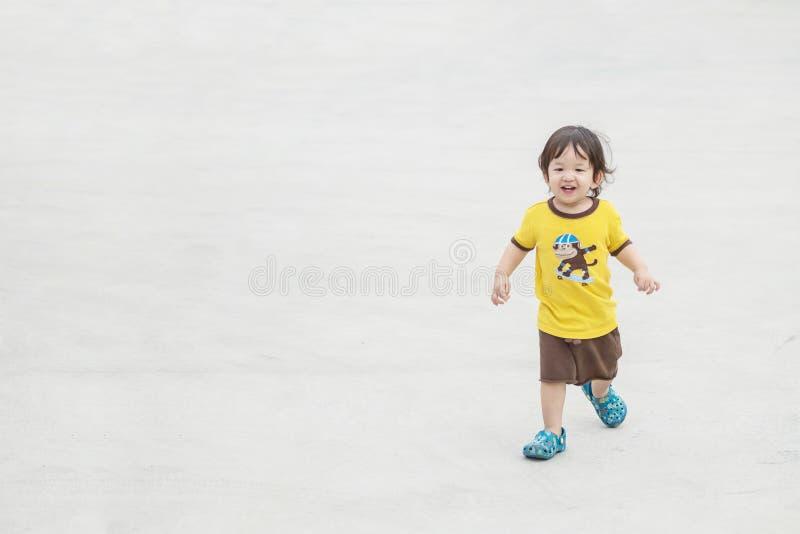El niño asiático lindo del primer que jugaba en piso del cemento en el aparcamiento texturizó el fondo con el espacio de la copia foto de archivo