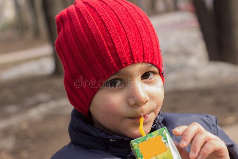 El niño bebe el jugo en el patio Retrato emocional del primer fotos de archivo