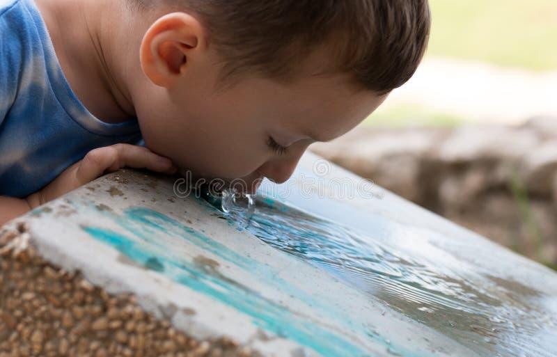 El niño bebe la agua fría de un refrigerador en un parque foto de archivo