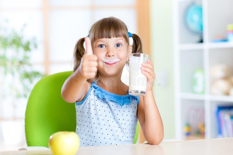 El niño bebe la leche y el mostrar pulgar para arriba foto de archivo