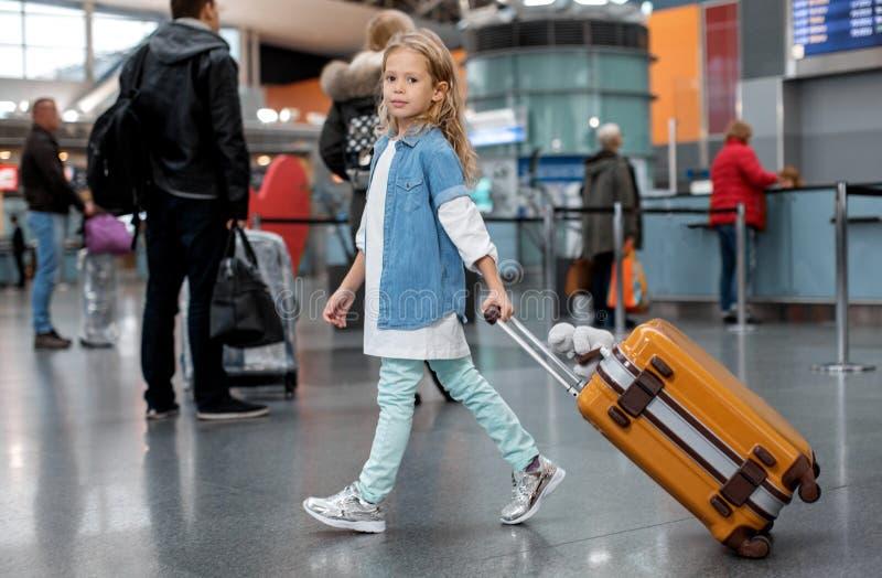 El niño bonito positivo está sosteniendo su equipaje imagenes de archivo