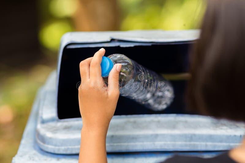 El niño cae la botella plástica foto de archivo