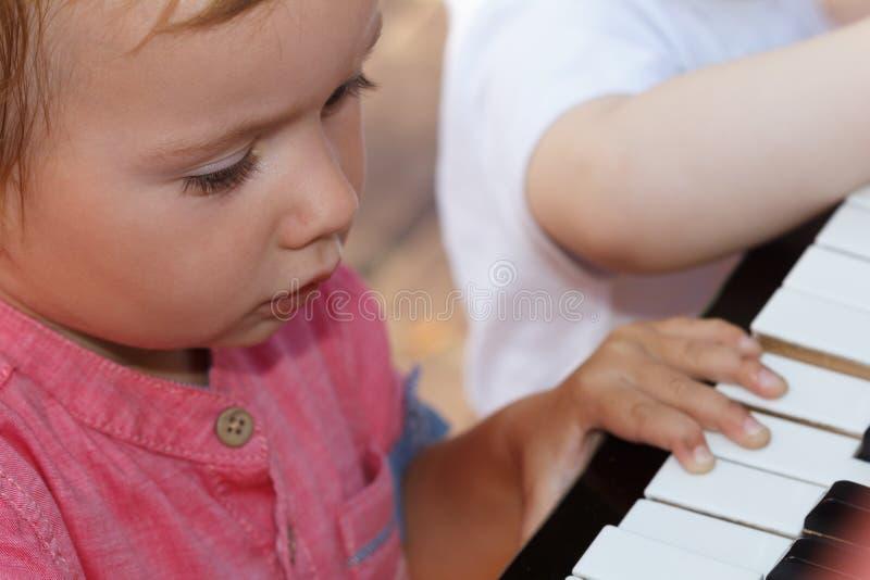 El niño canta una canción y juega el piano, niñez feliz fotos de archivo