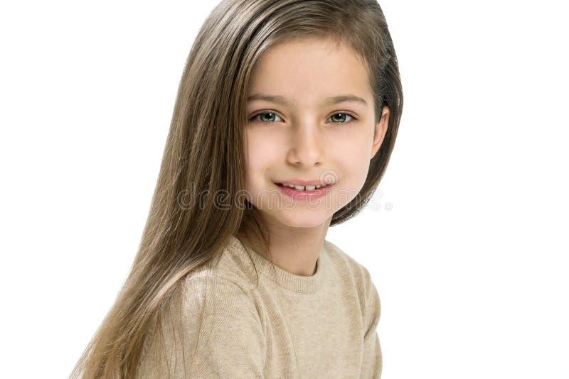 El niño caucásico de la muchacha 7-8 años, con el pelo recto largo en el fondo blanco, copia el espacio imagenes de archivo