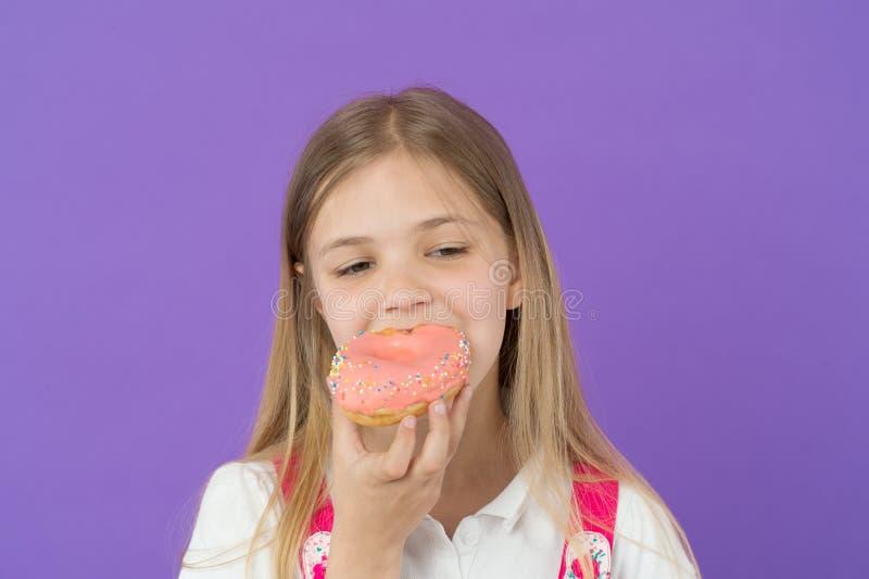 El niño come el buñuelo en el fondo violeta Buñuelo esmaltado mordedura del anillo de la niña Concepto de Candyshop niñez y felic fotografía de archivo