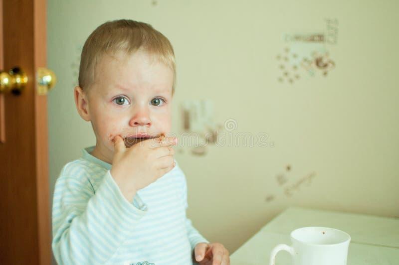 El niño come con los rasgones imagen de archivo libre de regalías