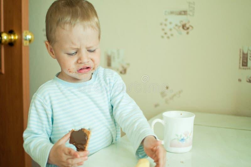 El niño come con los rasgones foto de archivo