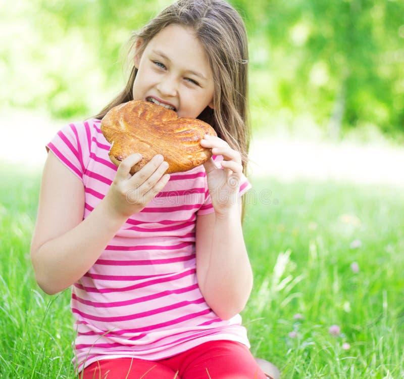 El niño come el mollete foto de archivo libre de regalías
