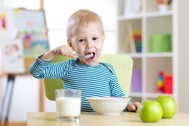 El niño come la comida sana en casa o la guardería fotos de archivo