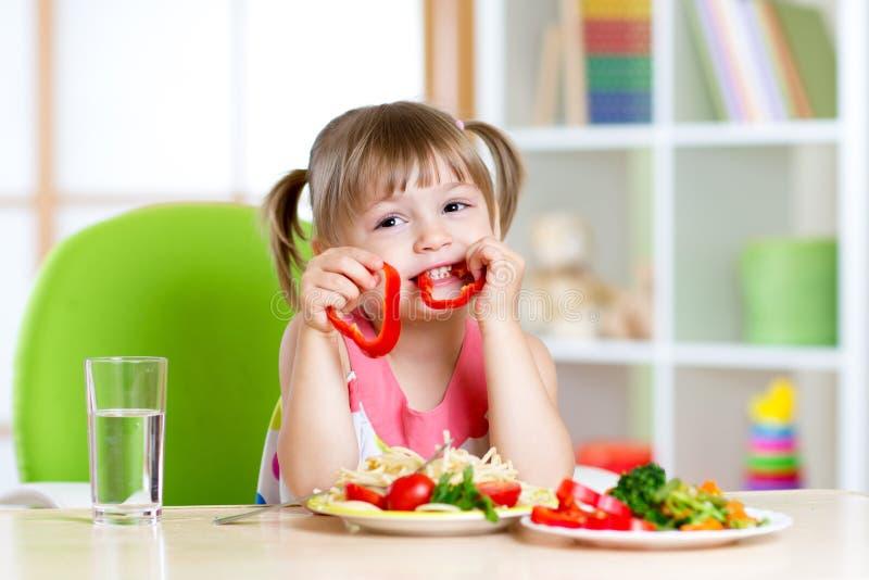 El niño come la comida sana en guardería o en casa fotografía de archivo libre de regalías