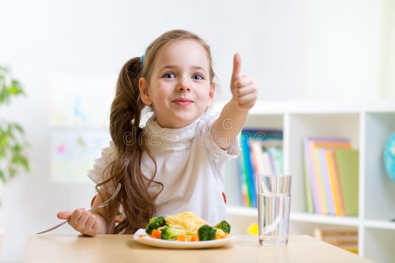 El niño come la comida sana que muestra el pulgar para arriba foto de archivo