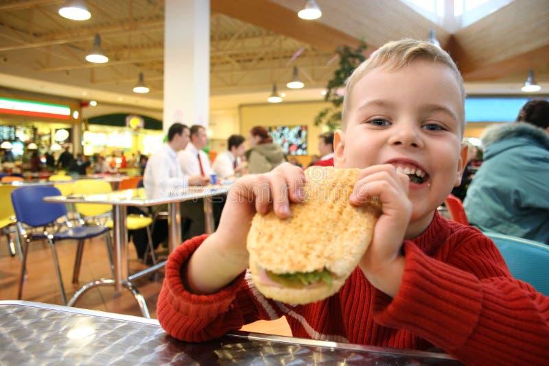 El niño come la hamburguesa imagenes de archivo