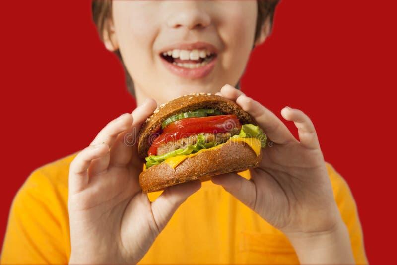 El niño come la hamburguesa en fondo rojo Niño masculino con la hamburguesa imagen de archivo