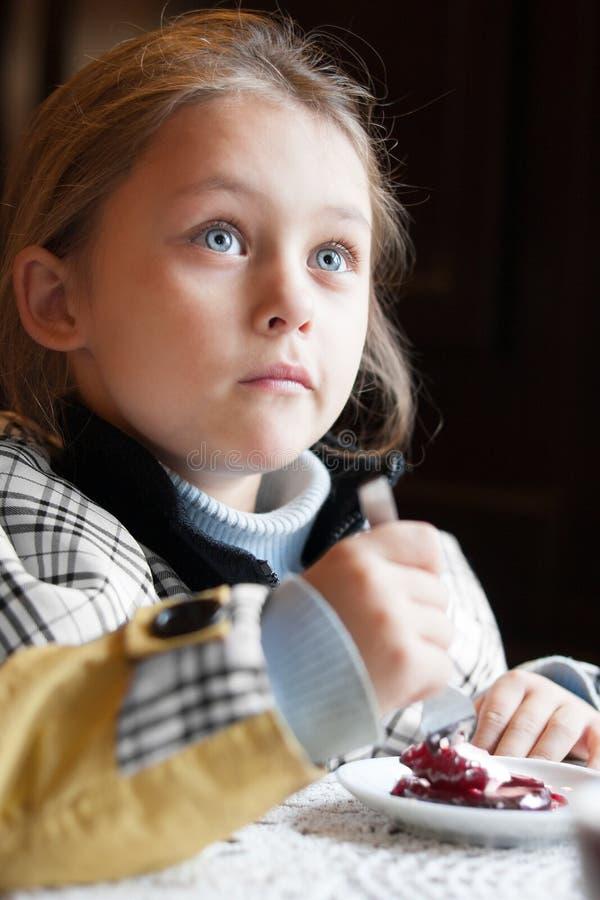 El niño come un postre en café fotografía de archivo