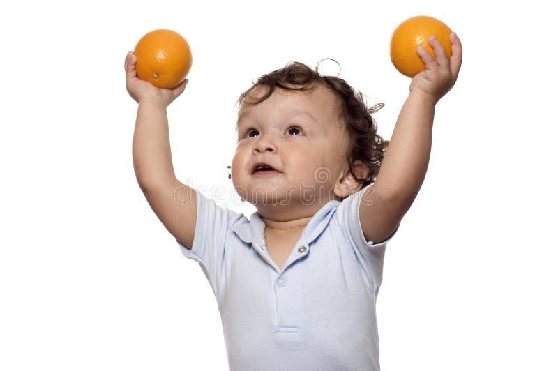 El niño con las naranjas. imagen de archivo