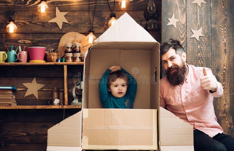 El niño con el paquete del jet finge ser astronauta Niño que juega con el padre Papá e hijo felices foto de archivo libre de regalías