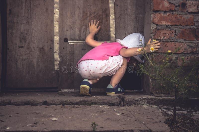 El niño curioso que miraba en el agujero oscuro en puerta de granero en campo vertió curiosidad del concepto fotografía de archivo