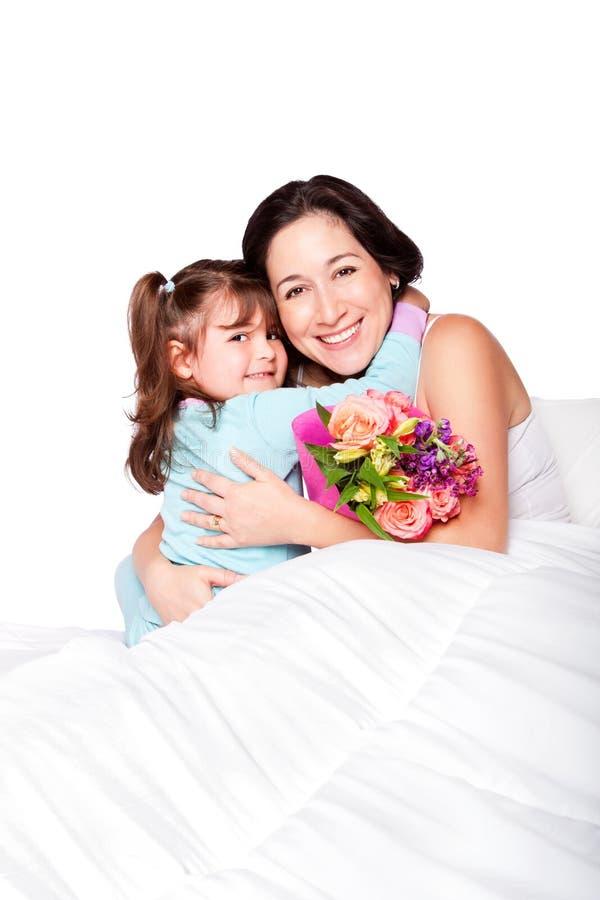 El niño da las flores a la madre en cama imagen de archivo